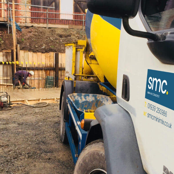 SMC Team Member Laying Concrete With Truck in Forefront